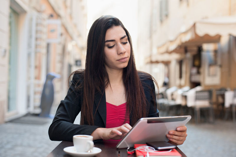 Young businesswoman in the city Black Hair Businesswoman Cafe Time City Day Front View Lifestyles Mobile Phone Outdoors Portrait Pretty Tablet Urban Woman Working Young
