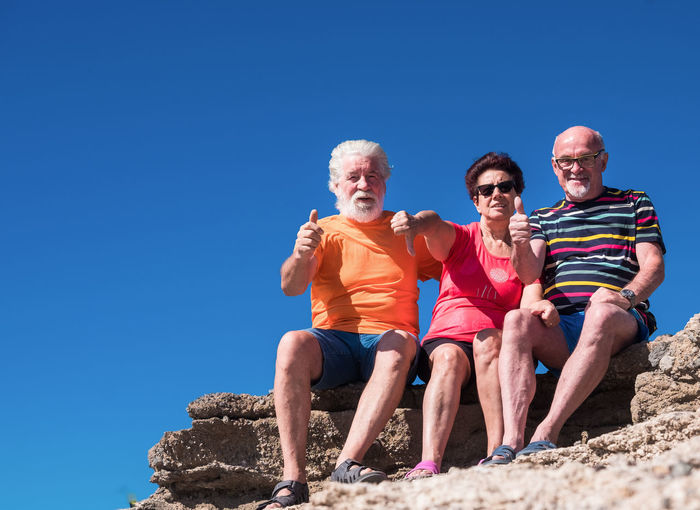 Senior friends gesturing while sitting on rock against clear blue sky