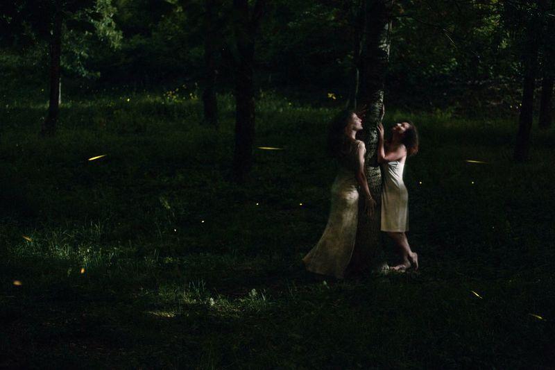 Women standing on field by tree