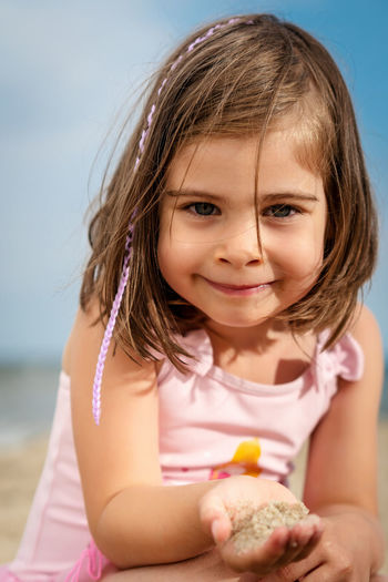 Portrait of smiling girl holding sand at beach
