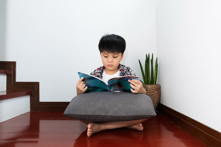 Portrait of boy sitting on chair at home