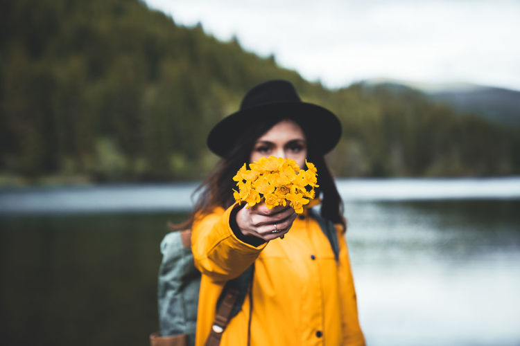 Close up view of female backpacker with hat and yellow jacket handing wild flowers