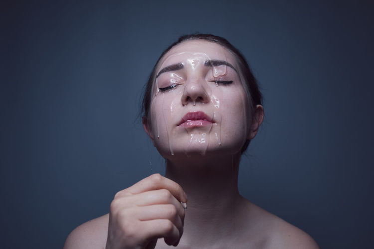 Close-up of shirtless young woman with beauty product on face against gray background