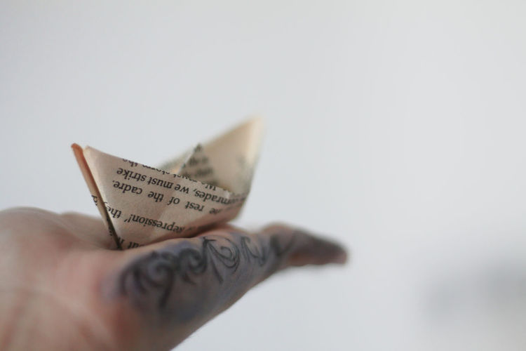 a new beginning awaits The Week on EyeEm No People Travel Conceptual Conceptual Photography  Travel Concept Copy Space Soft Focus A New Beginning Human Hand White Background Paper Newspaper The Media Close-up Origami Chance Paper Boat