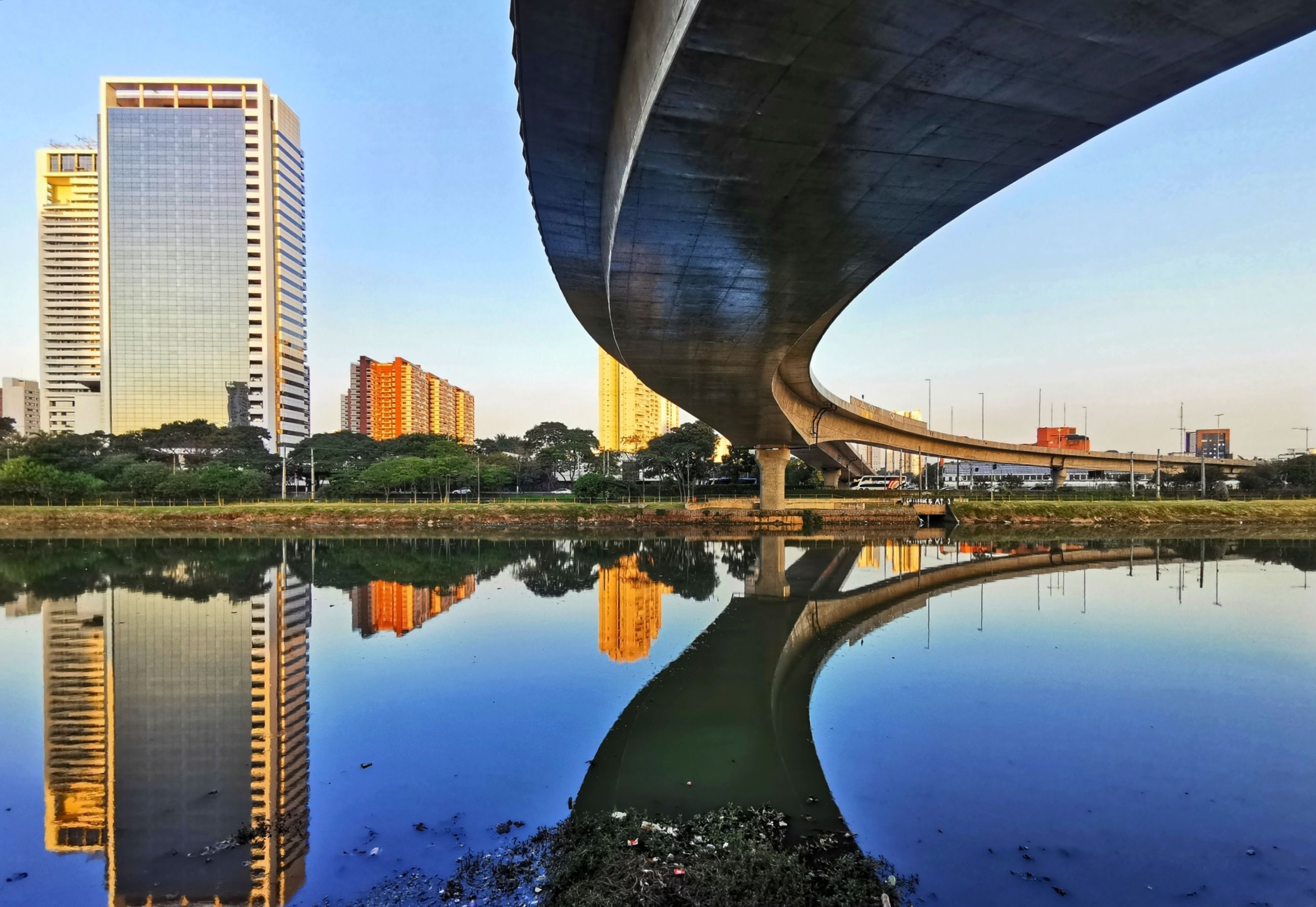 architecture, built structure, water, reflection, building exterior, bridge, sky, river, connection, bridge - man made structure, city, nature, waterfront, building, no people, office building exterior, day, transportation, clear sky, outdoors, skyscraper, modern, cityscape, arch bridge