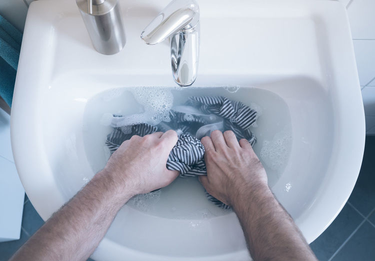 Cropped Hands Of Man Washing Clothes In Sink