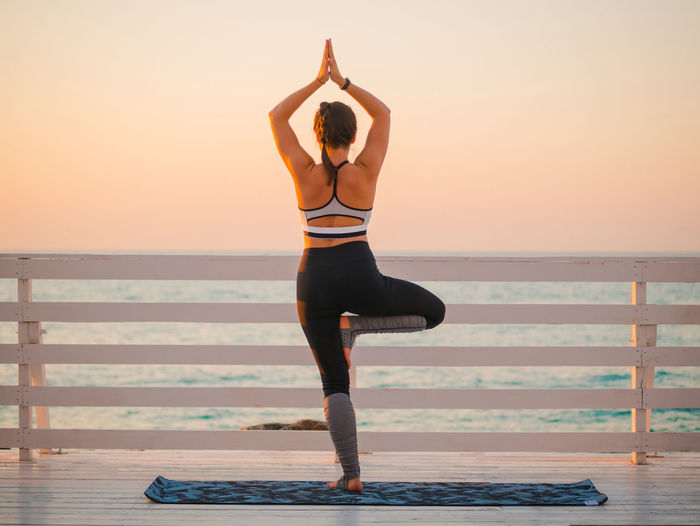 Full Length Of Woman Exercising Against Sky During Sunset