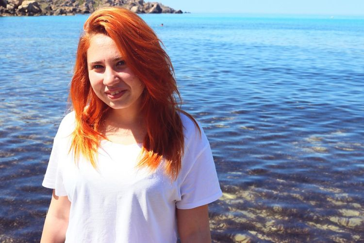 Portrait of redhead woman standing against sea
