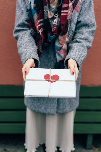 Midsection of woman holding package with heart shape