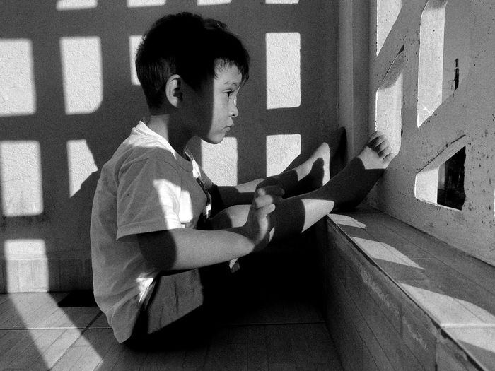 Side view of boy sitting against wall