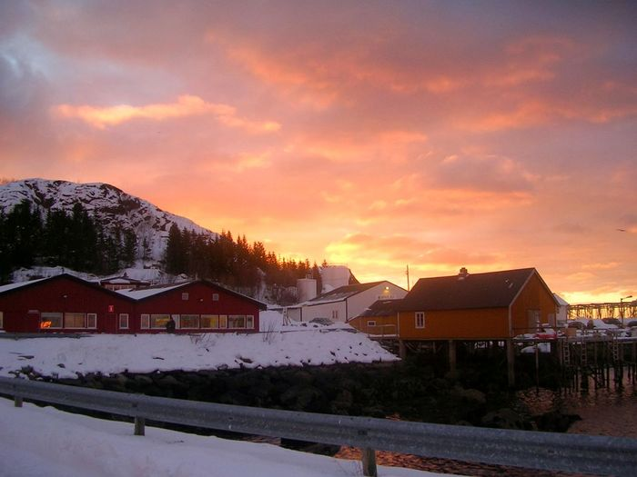 Snow covered houses by buildings against sky during sunset