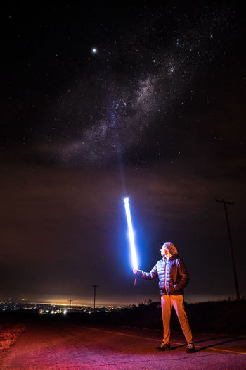 Full length of young woman standing against sky at night