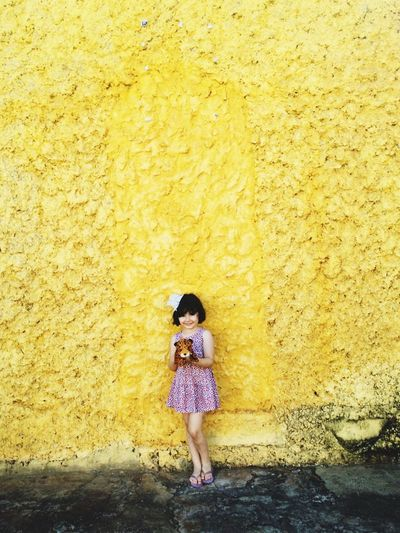 Full length of girl standing on a yellow wall