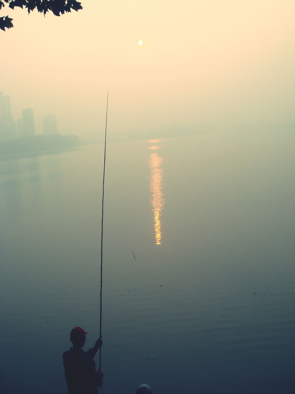 fishing, water, fishing pole, tranquil scene, tranquility, silhouette, sea, nature, sunset, outdoors, beauty in nature, weekend activities, standing, scenics, clear sky, one person, men, real people, sky, day, people