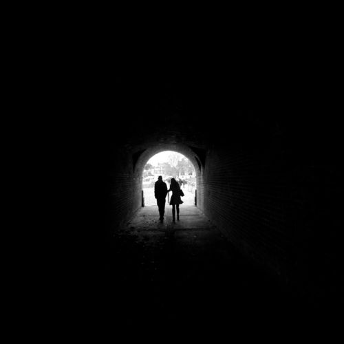 Rear view of silhouette people walking in tunnel