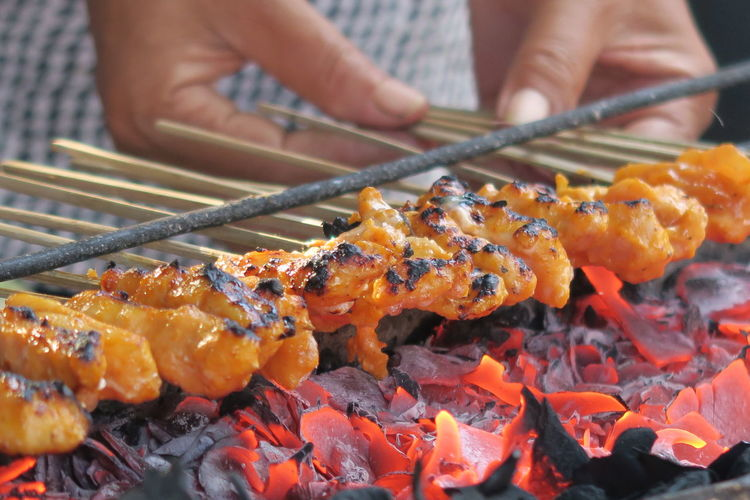 Close-Up Of Person Cooking Food On Fire