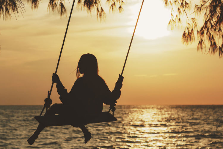 Silhouette woman swinging against sea during sunset
