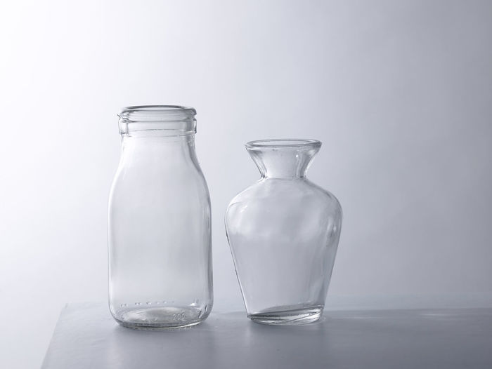Close-up of empty glasses on table against white background