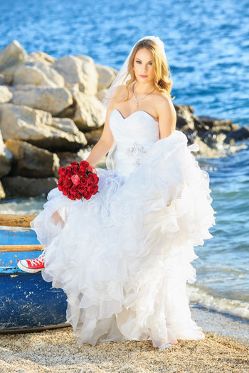Portrait of bride holding rose bouquet while standing at beach