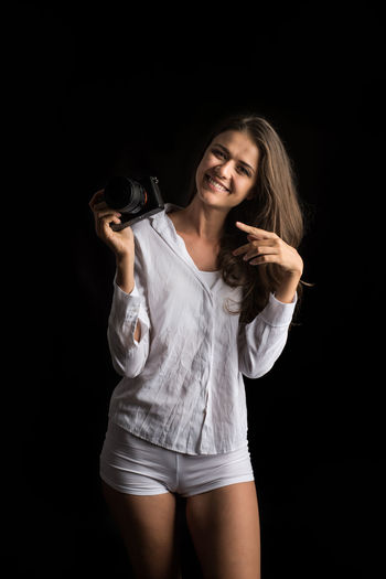 Portrait Beautiful Woman Smiling Beauty Happiness Looking At Camera Young Adult Black Background Hair Women Three Quarter Length Cheerful One Person Studio Shot Beautiful People Emotion Adult Young Women Casual Clothing Holding Hairstyle Positive Emotion Shorts