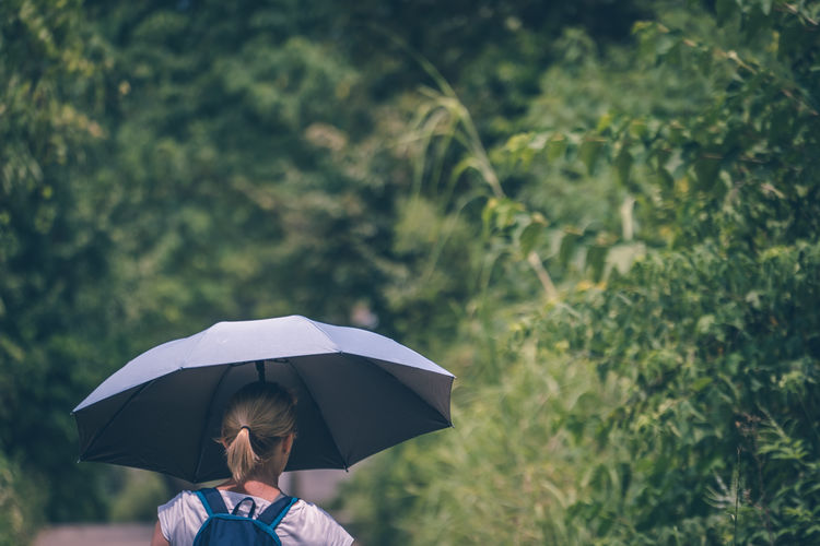 Rear view of woman holding umbrella