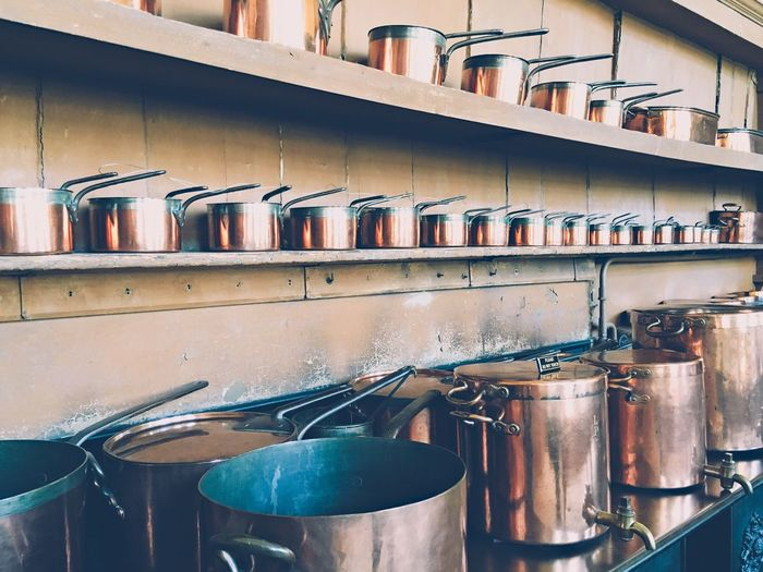 Copper Utensils Arranged On Shelf In Kitchen