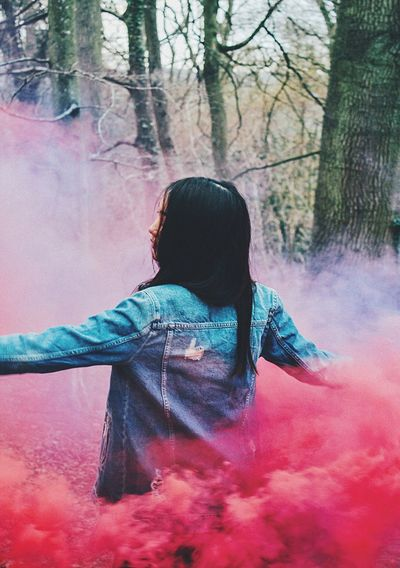 Rear view of woman amidst red smoke at forest
