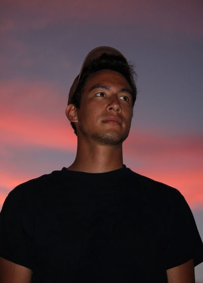 Portrait of young man looking away against sky during sunset