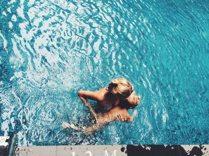 Portrait Of Woman Swimming In Pool With Son