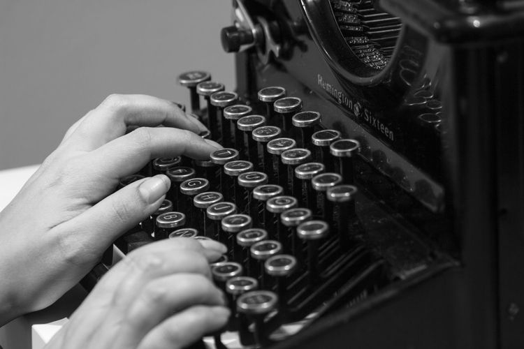 Close-Up Of Woman Using Typewriter