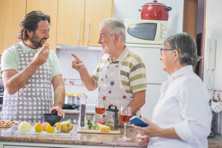 Happy Family Preparing Food While Talking In Kitchen