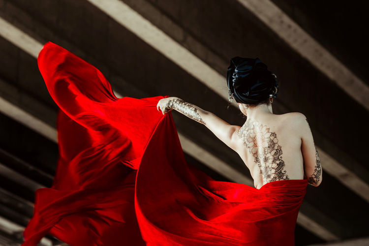 Rear View Of Tattooed Seductive Fashion Model Holding Red Fabric