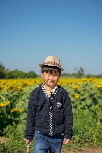 Portrait of smiling girl standing on field against sky