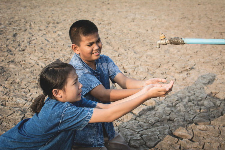 Siblings With Hands Cupped Below Tap On Cracked Field