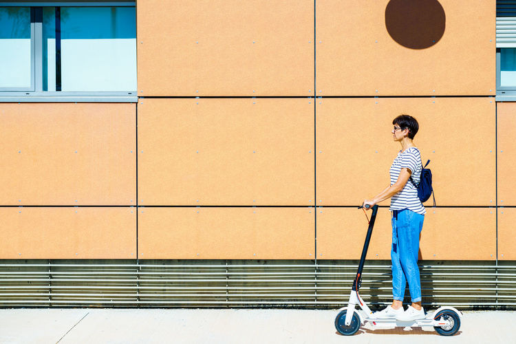 Side view of woman standing on electric push scooter against building