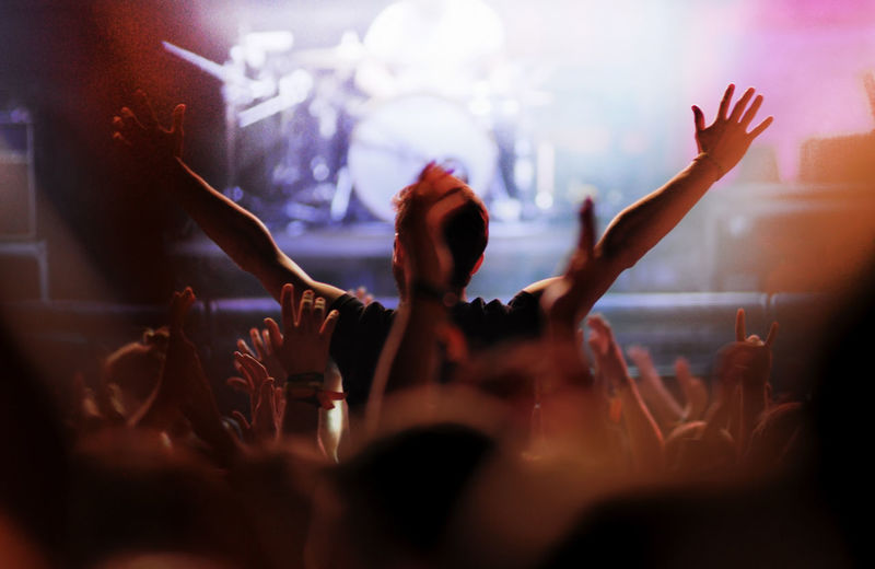 Rear view of man with arms outstretched at concert