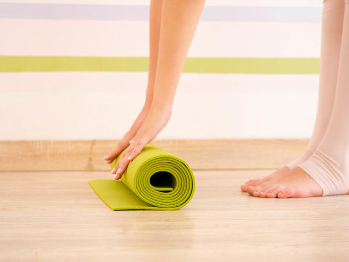 Low Section Of Woman Folding Exercise Mat On Hardwood Floor