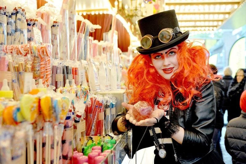 Portrait of young woman dressed up in steam punk standing at shop