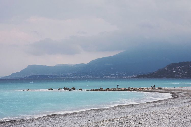 View Of Sea With Rocks By Mountains Against Cloudy Sky