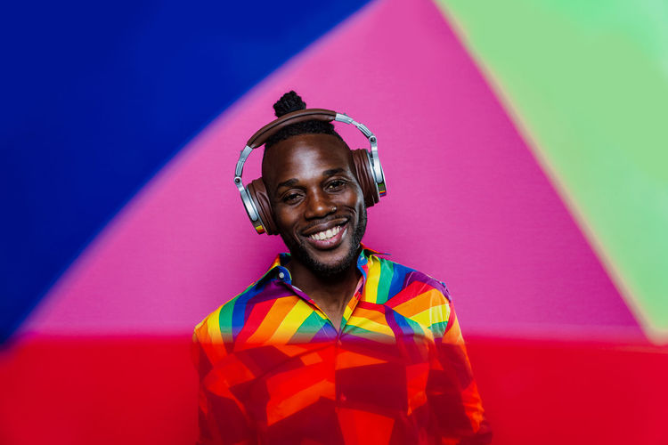 Portrait of smiling young man standing against multi colored background