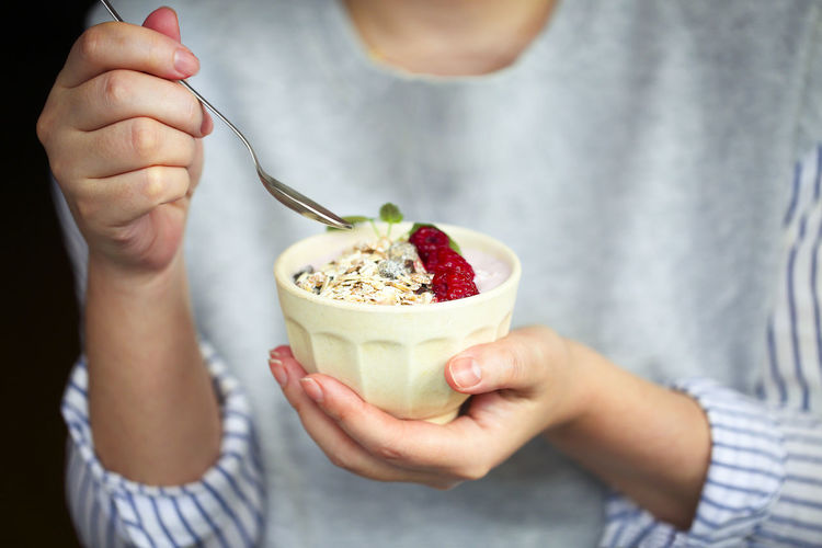 Midsection of woman holding food in bowl