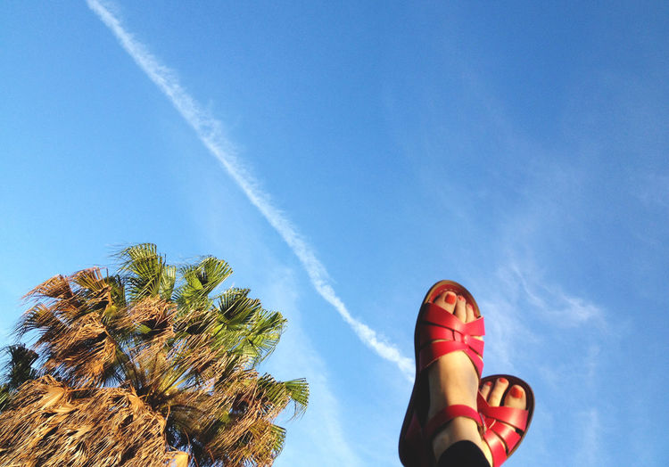 Low Angle View Of Woman With Feet Up Against Sky