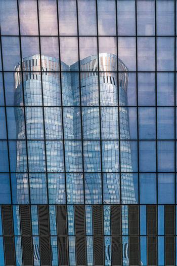Digital composite image of glass building against blue sky