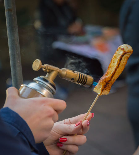Close-up of hand holding torch melting a cheese stick
