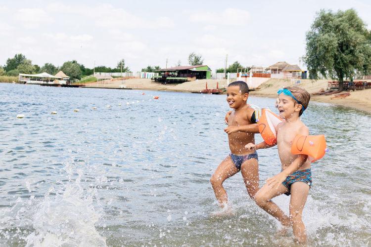 Cheerful shirtless boys running in sea