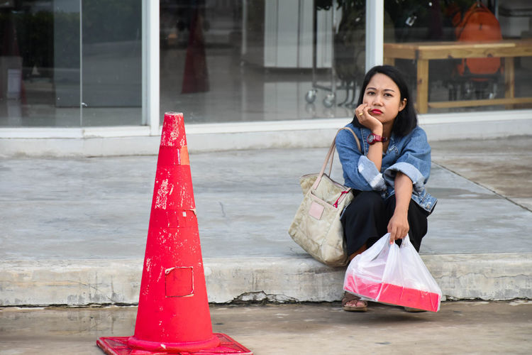 Portrait of woman holding plastic bag while sitting by red traffic cone on road