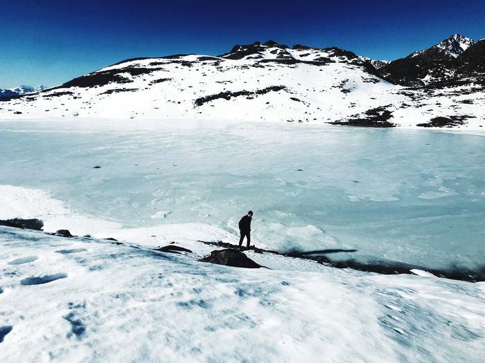A man exploring a frozen lake on the snowy mountain top