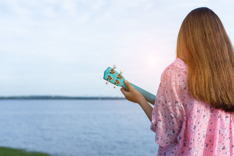 Rear view of young woman playing ukulele against lake and sky