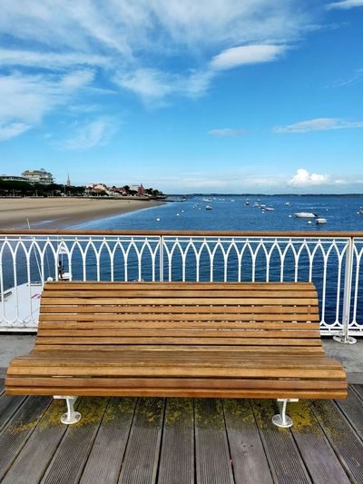 Wooden bench on sea shore against sky
