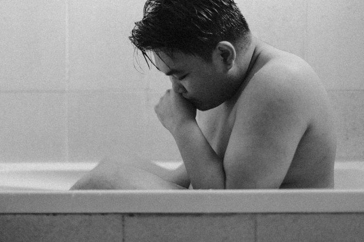 Side view of shirtless man sitting in bathroom